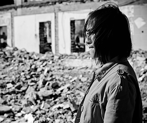 Image of woman among building rubble of war