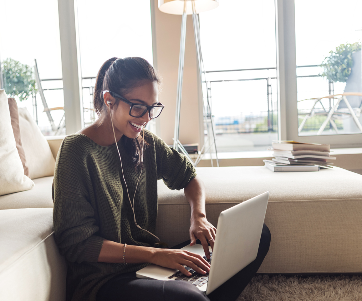 Photo of woman using laptop near couch