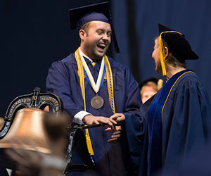 Photo of UNCG graduate receiving diploma in front of the University Bell