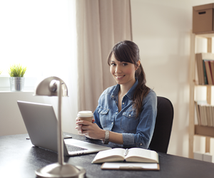 Woman Holding Coffee Cup in Front of Laptop