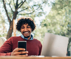 Man smiling in front of phone with laptop