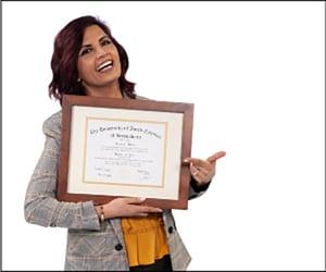 Samira Khan smiling and holding diploma