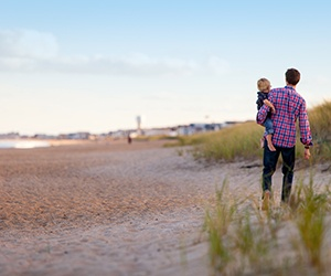 Man and child walking on beach.jpg