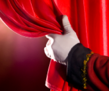 Photo of hand pulling back stage curtain