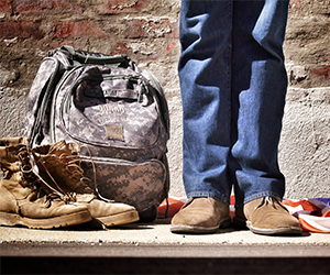Photo of military backpack, boots and person's legs and shoes